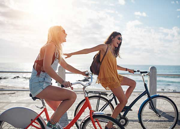 2 woman riding bikes on the strand by the beach