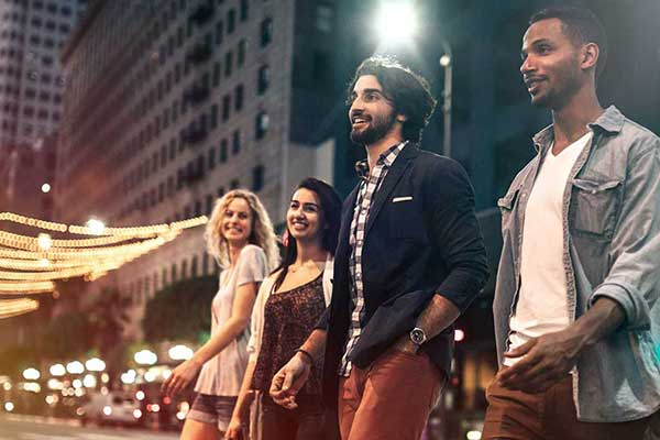 Group of friends walking in the street at night