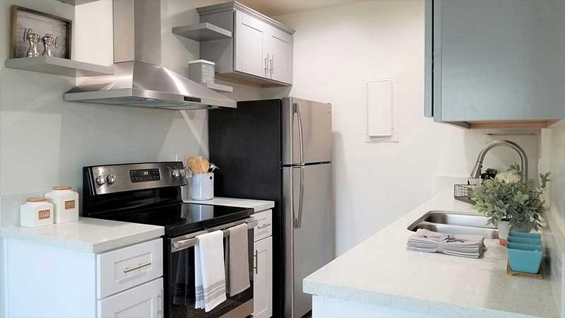 Kitchen stove and refrigerator interior photo of Bleu Apartments